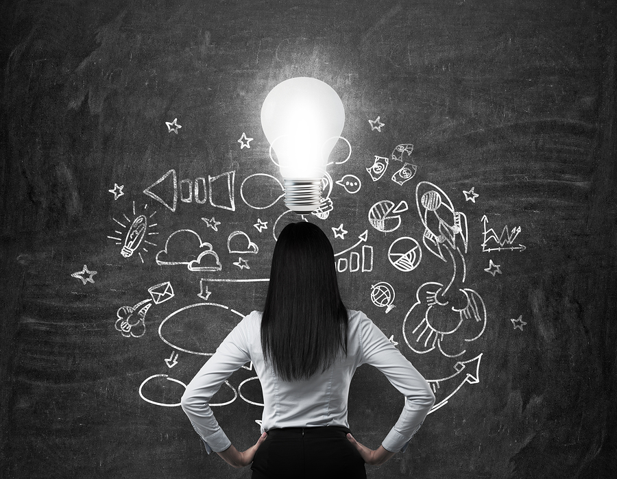 Rear view of the brunette business lady who is looking for new business ideas. Drawn business icons on the black chalk board and a light bulb as a concept of new idea.
