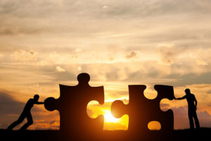 Two men connect two puzzle pieces. Sunset sky. Concept of business solution, teamwork, solving a problem, challenge