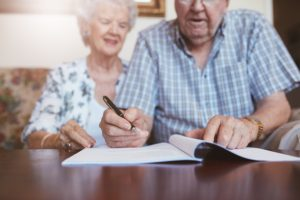 Senior couple signing will documents. Elderly caucasian man and woman sitting at home and signing some paperwork focus on hands.
